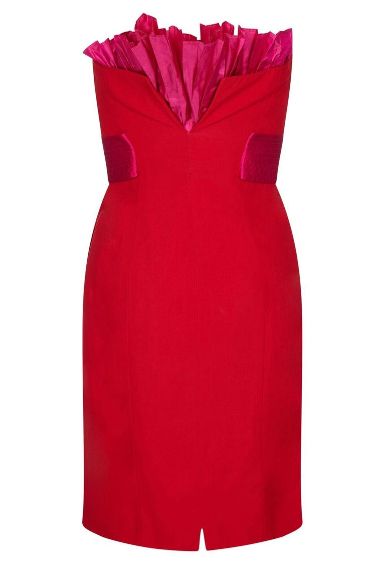 This arresting 1980s crimson silk cocktail dress by Gianfranco Ferre is of excellent quality and features a show-stopping design. The piece combines stylish simplicity with flamboyant, innovative tailoring. At first glance we see a knee length