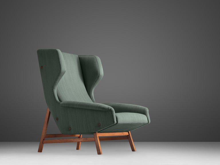 Gianfranco Frattini for Cassina, lounge chair model 877, blue fabric and teak, Italy, circa 1959.  Sturdy and voluminous lounge chair in blue original fabric. This wingback chair shows nice details and elegant lines. The buttons on the outside of
