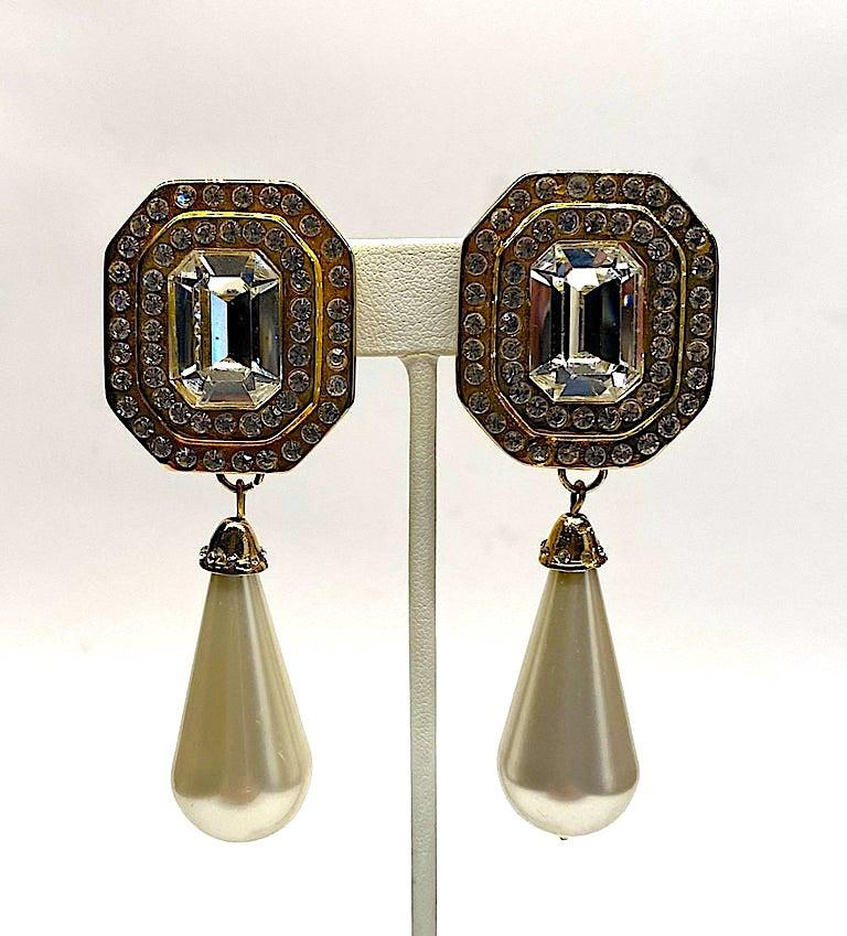 A large statement pair of 1980s gold tone rhinestone and faux pearl pendant earrings by Italian fashion jewelry company Gianni Di Liguoro. The octagon shape top piece is 1.13 inches wide and 1.38 inches long. It is set with a 12 x 17 mm emerald cut