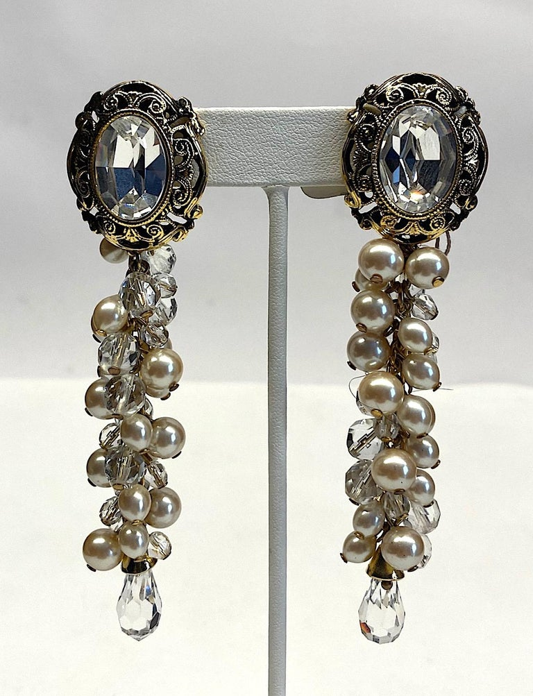 A dramatic pair of earrings by Italian fashion jewelry company De Liguoro circa 1980. Champagne color faux pearls with large and small faceted crystal beads are individually attached to a gold tone chain in a cluster formation. The chain of beads is
