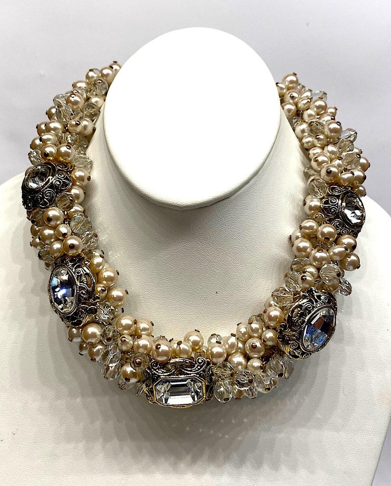 A dramatic necklace by Italian fashion jewelry company De Liguoro circa 1980. Champagne color faux pearls with large and small faceted crystal beads are individually attached to two gold tone chains in a cluster formation. Additionally, within the