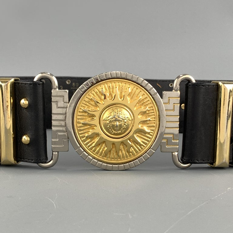 Vintage GIANNI VERSACE belt features a thick studded black leather strap with gold tone Medusa heads, metal loops, and round Medusa Sun medallion buckle. Made in Italy.  Very Good Pre-Owned Condition. Marked: 80/32  Length: 30 in. Width: 2 in. Fits: