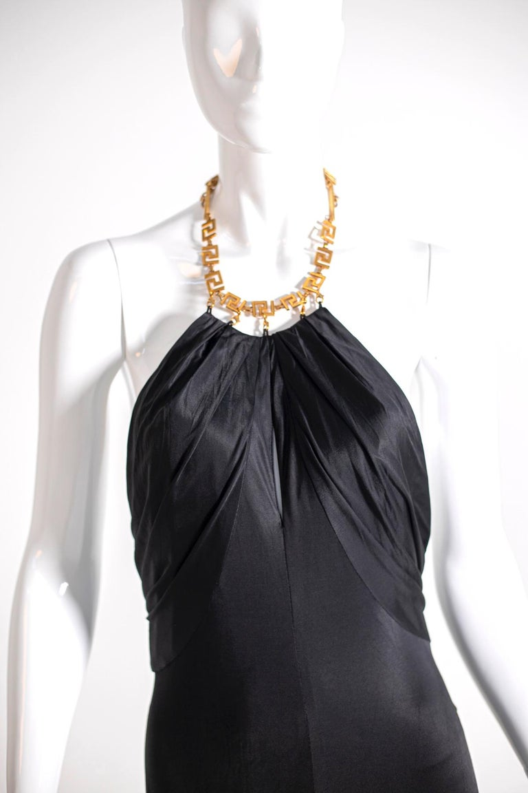 Wonderful black short evening dress, by the famous designer Gianni Versace 1990's, in very soft Viscosa 100%. The dress has an open back and an American-style neckline made with a golden metal strap, in the final part, behind the neck, has a chain