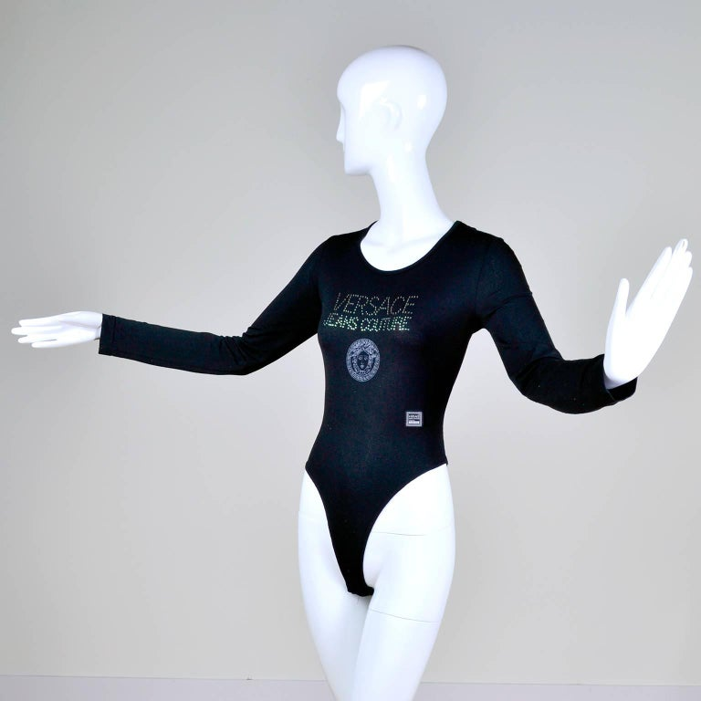 This vintage Gianni Versace Jeans Couture bodysuit has the words Versace Jeans Couture embellished on the top of the bodysuit and the medusa logo in the center.  This rare black Versace top has a front label that reads; Versace Jeans Couture Piece