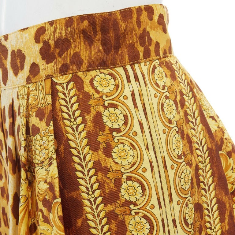 GIANNI VERSACE brown leopard gold baroque rococo print flared mini skirt IT42 M  GIANNI VERSACE VINTAGE 100% silk. Brown leopard base. Gold baroque rococo crown print. Pleated skirt. Flat waistband. Concealed zip back closure. Flared skirt. Made in