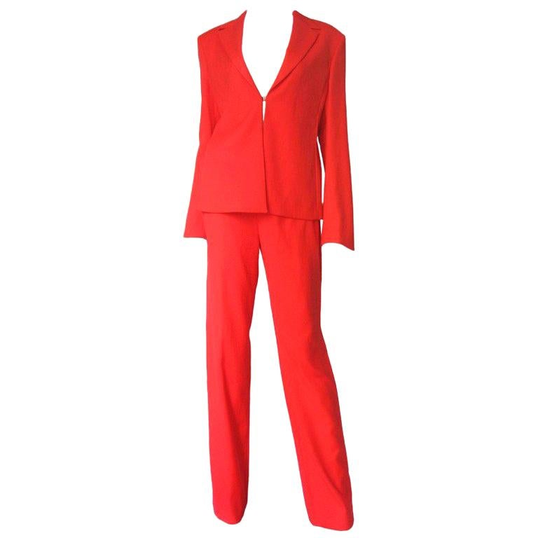 A gorgeous orange light weight suit from Gianni Versace Couture.  The V neck jacket has a front hook closure and lightly padded shoulders.  The straight leg mid rise pants have 2 fine curved nude mesh covered cut outs at each side upper hip.  Both