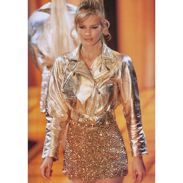 This is an absolutely Incredible Fall Winter 1994 / 95 motorcycle style cropped gold leather jacket with a belt from Gianni Versace. This style of moto jacket was featured on the runway and worn by Claudia Schiffer as shown in the photo.    The