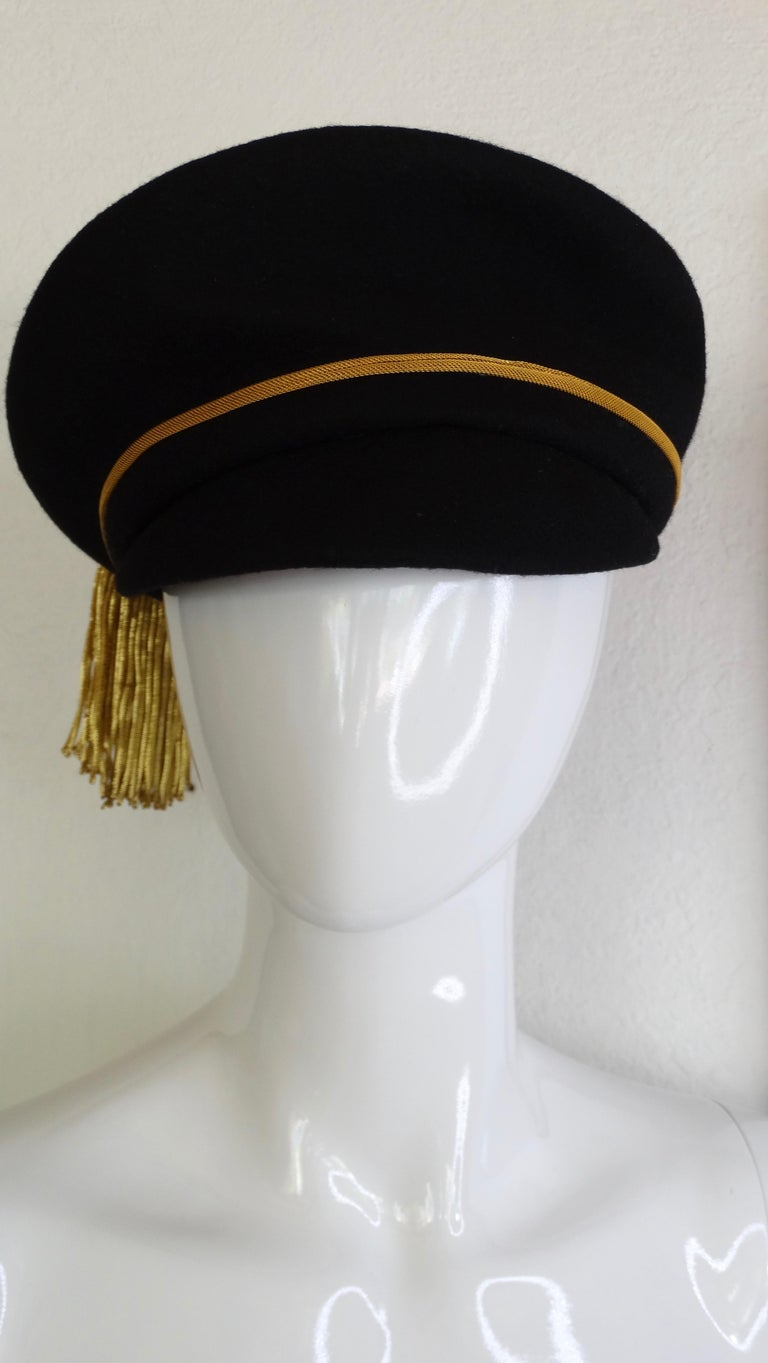 Complete your hat collection with this extremely rare Versace hat! Circa 1990s, this black felt train conductor style hat features a gold trim and large gold threaded tassel which hangs from a 24K Medusa embossed medallion framed with black