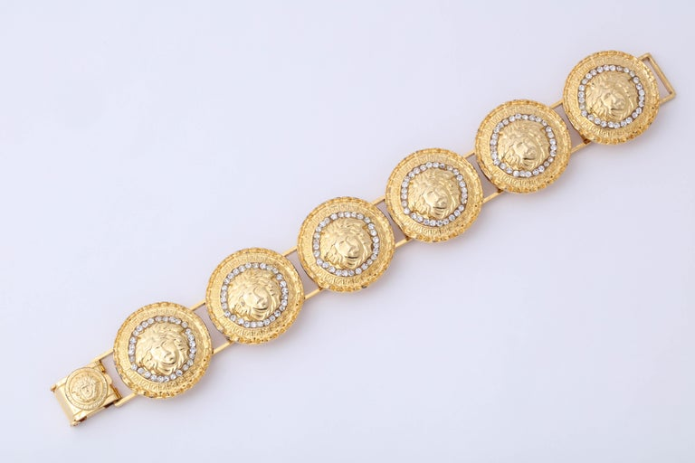Gianni Versace gold toned bracelet with rhinestones and 6 iconic Medusa motifs.