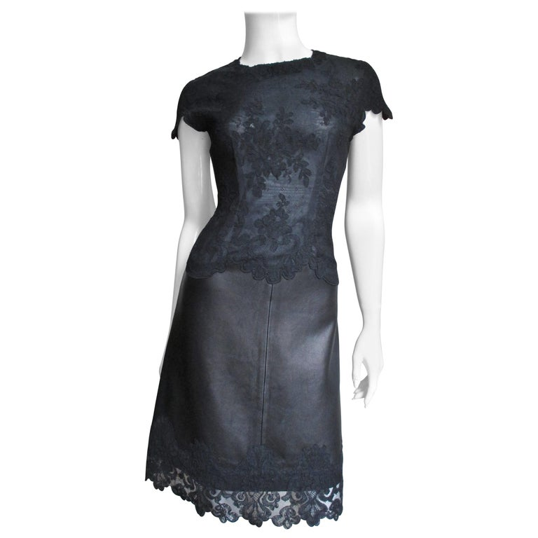 A fabulous black leather and lace dress by Gianni Versace.  It has flower pattern lace on top finishing following the scallop edges of the lace along the hem, cap sleeves and waist.  It is fitted through the bodice and has a subtle A line leather