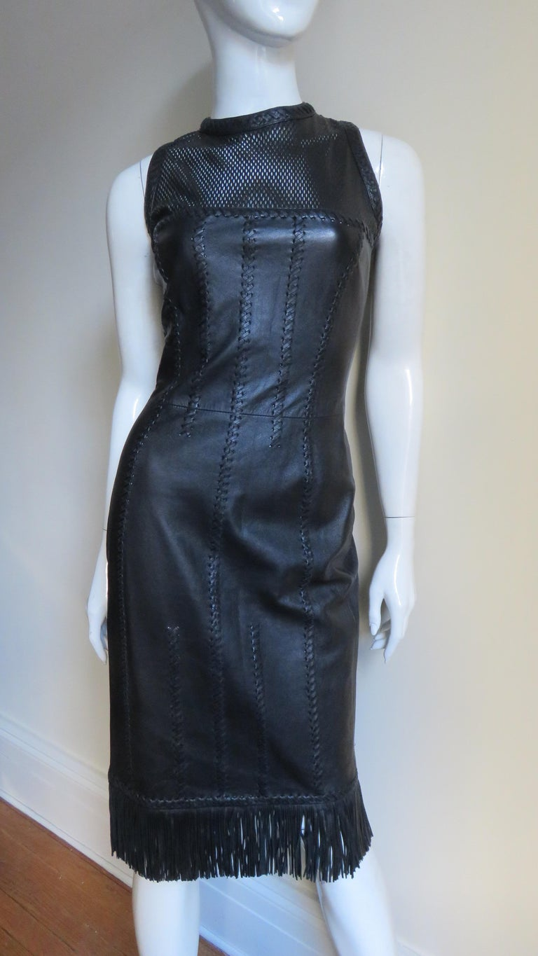 An extraordinary supple black leather dress from Gianni Versace 2002 Spring/Summer Collection.  This one has all of the bells and whistles- a fine fringe hem, laser leather perforated mesh at the upper chest and elaborate seaming highlighted with