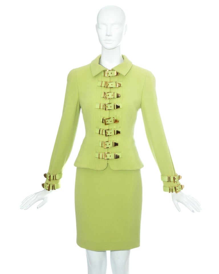 Gianni Versace; lime green wool bondage skirt suit. Structured jacket with 15 leather gold buckle fastenings, hidden zip fastening and silk lining. Sold with matching figure hugging pencil skirt.  Fall-Winter 1992  Image 5 and 6: Gianni Versace