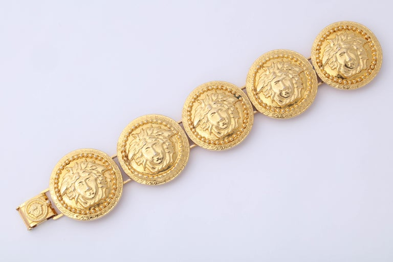 Gianni Versace gold toned bracelet with 5 iconic Medusas motifs.