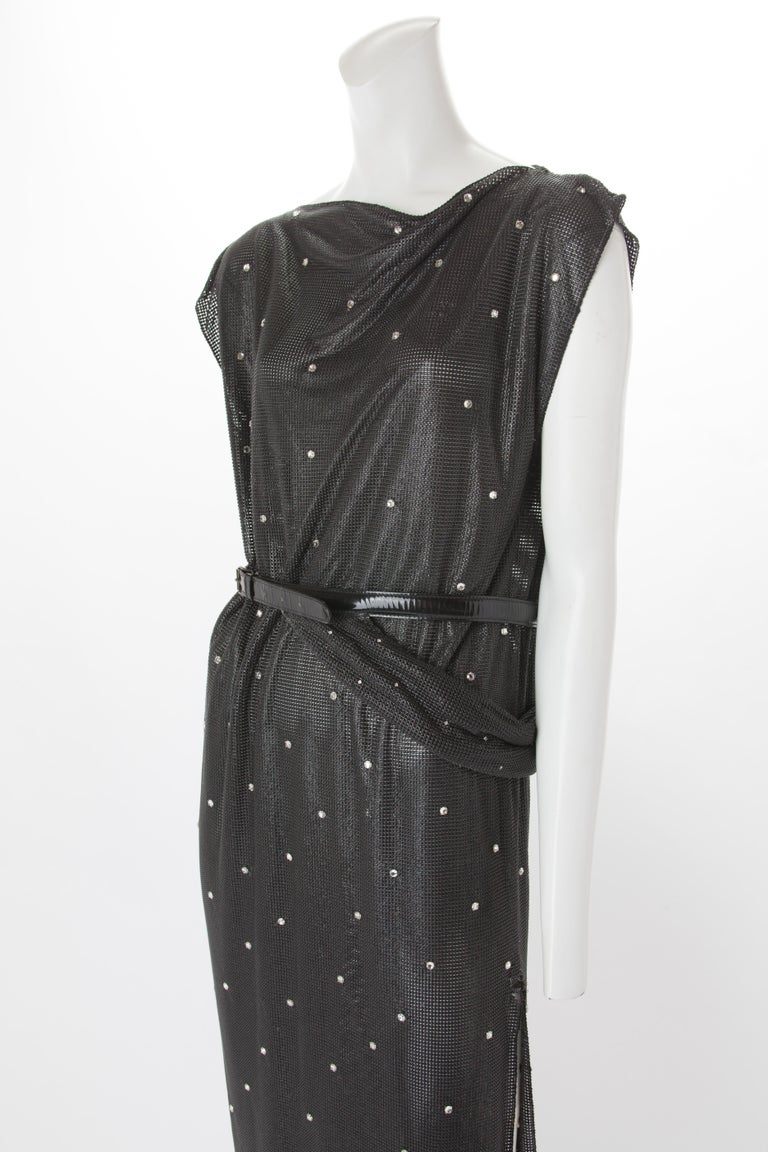 Gianni Versace Oroton Dress with Rhinestone Embellishment and Belt, c..1990s. Cowl neck dress featuring cap sleeve in gunmetal chainmail with asymmetrical hemline. Features silver rhinestone embellishments throughout.  Detachable patent leather belt