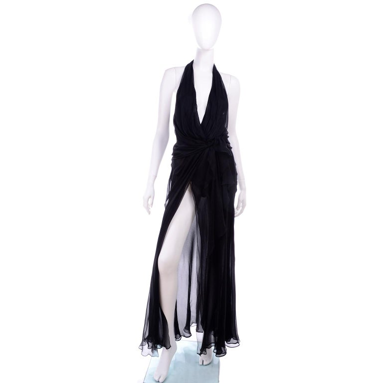 This is an absolutely stunning vintage Versace dress. This vintage black silk chiffon evening dress has a thigh high cut slit in the front that reveals the legs, and a deep plunging neckline.  We especially love the gorgeous sheer panel in the back.