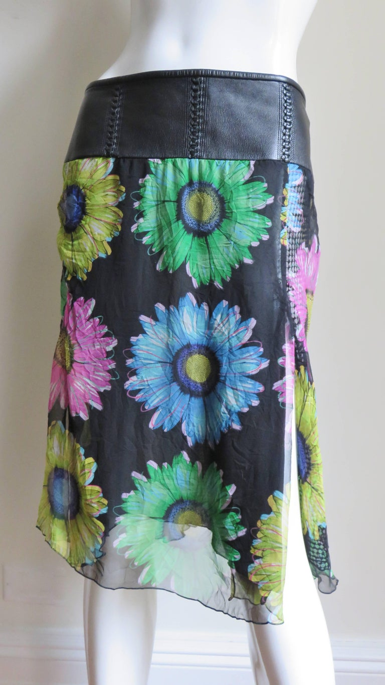 A gorgeous silk skirt with colorful flowers on a black background from Gianni Versace.  It has a wide leather waistband with intricately braided leather vertical lines.  The semi sheer silk has black silk lining under the front and back panels