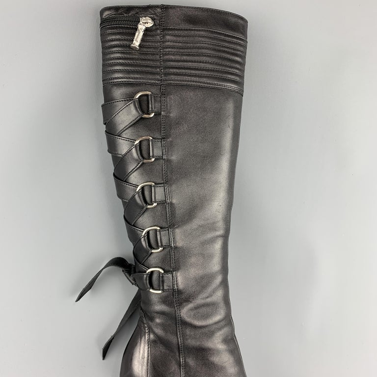GIANNI VERSACE Knee high bondage boots come in smooth black leather with a quilted top panel, pointed toe, stacked stiletto heel, and iconic Fall 2003 D ring corset lace up back. Made in Italy.   Excellent Pre-Owned Condition. Marked: IT 38