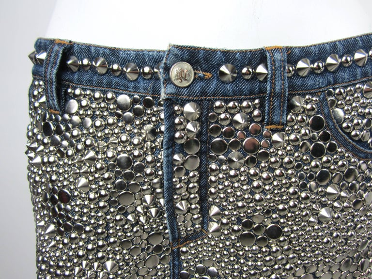 Stunning Versace skirt from the early 1990s. Totally Covered Skirt with silver studs of various sizes Zippered front, one-button closure Two patch pockets on the back Measuring 32 inches (Low Waist) on the waist 11.5 inches long. Labeled a size