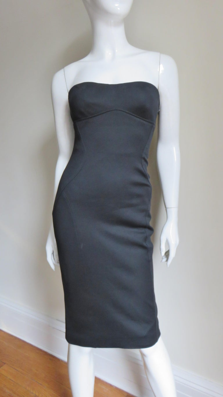 A fabulous black silk strapless dress from Gianni Versace Couture.  It has flattering intricate seaming under the bust and at the sides.  The back has fine leather laces with Medusa metal ends and elaborate grommets along it's length, adjustable and