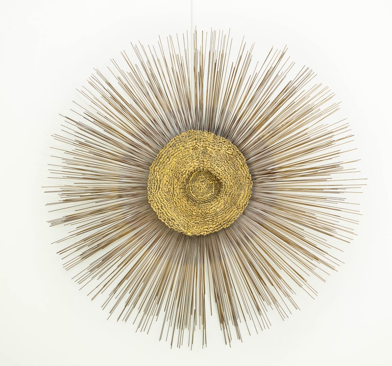 Giant 1970s Brutalist wall sculpture by Curtis Jere. The sculpture features a circular abstract design on top of radiating brass rods of varying lengths.