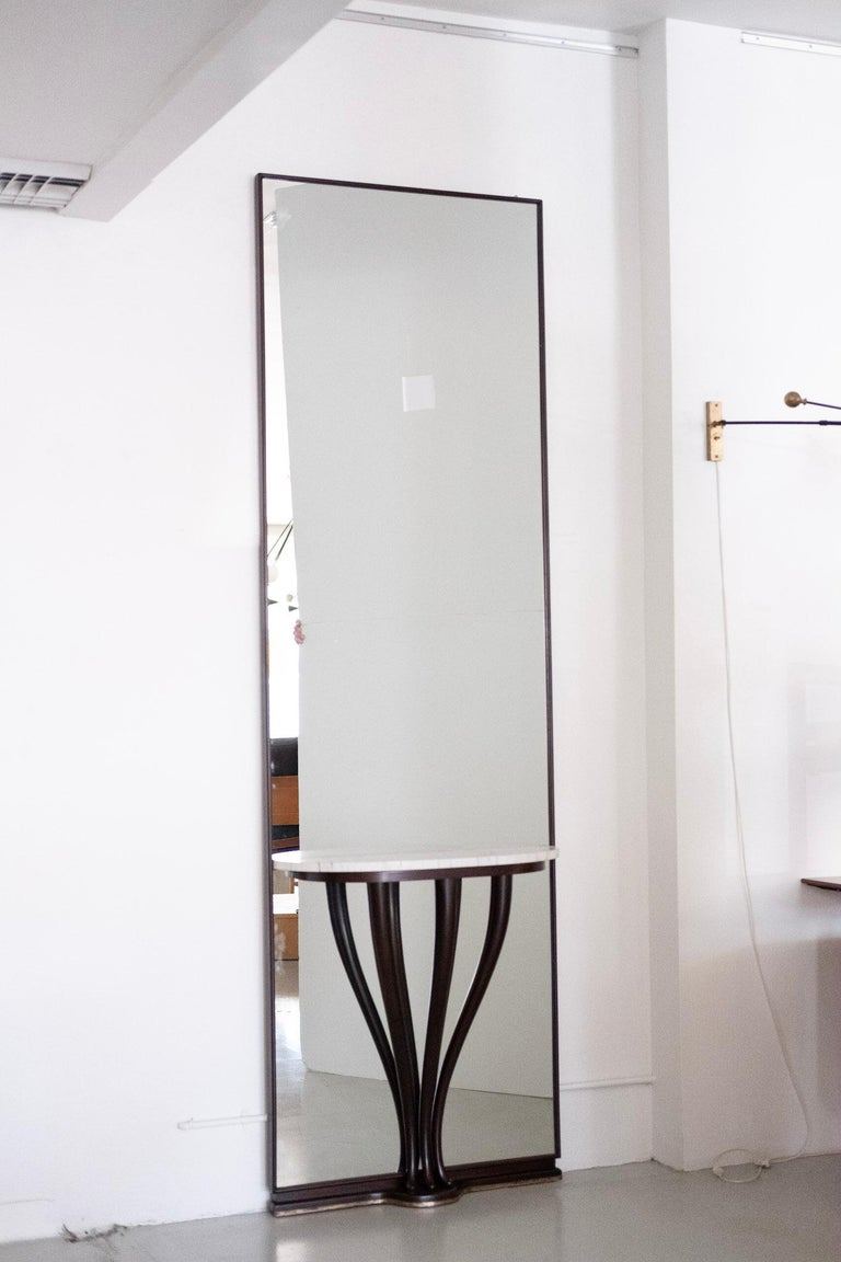 Stunning oversized floor mirror attributed to Fontana Arte. Sculptural mahogany legs with Carrara marble tabletop and base has brass inlay. Unique and impressive in size and scale.