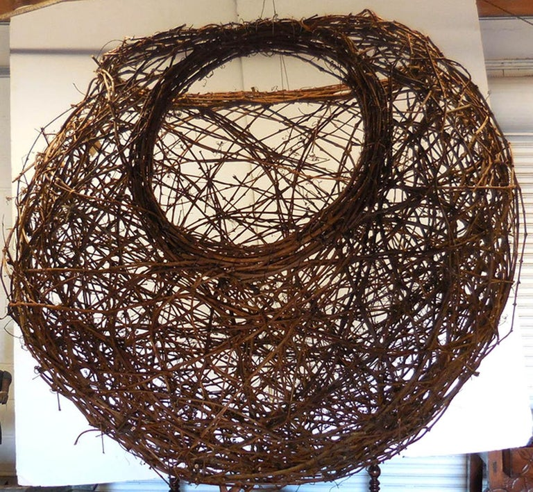 This basket like piece of woven grapevine can go inside or outside, on the ground or hung. Organic shape and materials. Great presence! Sphere with two openings. Would also look great as a large scale pendant light! Made by artist Matthew Culbert.