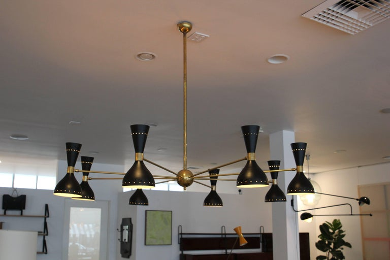 Gigantic ceiling light in 1950s Italian Stilnovo style. Large-scale brass and black metal shades, with eight articulating lampshades which light upward and down.  Incredibly crafted in Italy.