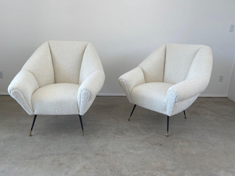 Wonderful pair of newly upholstered Italian chairs attributed to Gigi Radice  Great sculptural shape and large in scale Iron and brass legs - new shearling -like boucle upholstery.