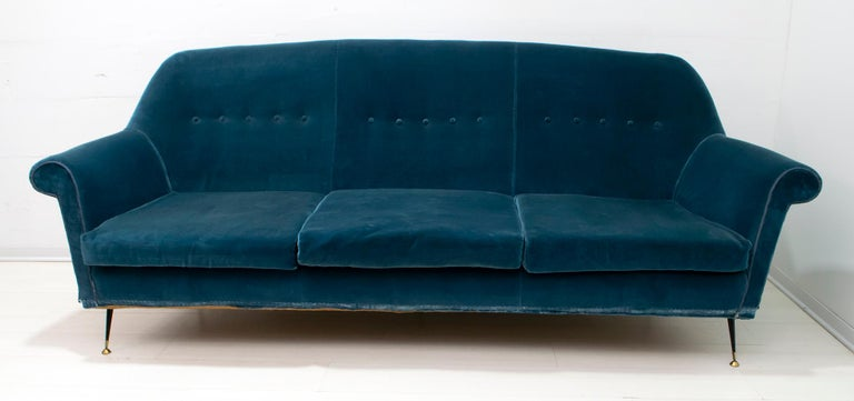 Sofa and two armchairs designed by Gigi Radice for Minotti. Made with solid wood structure and blue velvet covering and legs in brass and black lacquered metal. It is recommended to replace the lining, as shown in the photo is worn.