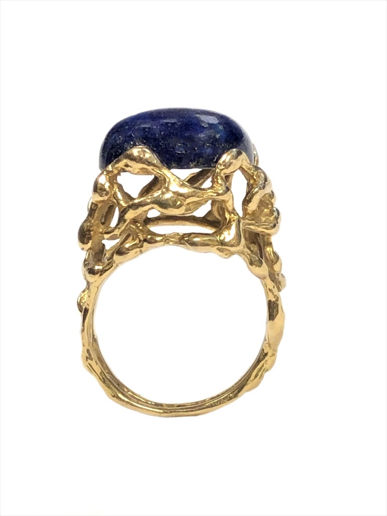 Circa 1970 Modernist Designed 18K Yellow Gold Ring by Gilbert Albert, centrally set with a Lapis Lazuli, the top of the ring measures 5/8 inch in diameter, finger size 6.