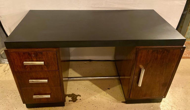 Gilbert Rohde Art Deco ebony top Mid-Century Modern desk or writing table having chrome pulls. This stunning ebonized modernist and rosewood desk has expandable pull out hide a way side that extend the surface to an astounding 82 inches wide. Having