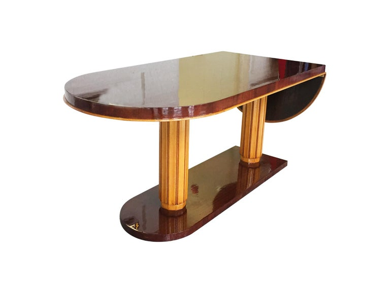 A superb drop-leaf desk by the American designer Gilbert Rohde, circa 1930s-1940s. The desk is crafted from mahogany and beech wood that are newly re-lacquered. The new finish gives the warm red-brown and orange tones of the wood a smooth gloss.