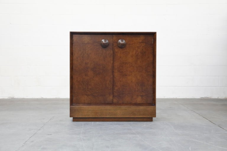 This fully-restored Classic and collectible burl wood dresser cabinet by Gilbert Rohde for Herman Miller was part of his 1941 'Paldao' line of streamline modernist and modular furniture. This two-door cabinet is most notable for its distinctive
