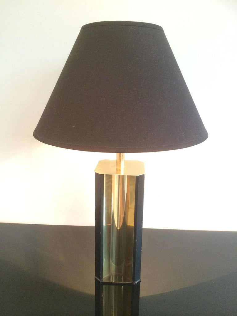 This table lamp is made of gilt metal and black lacquered wood. It has a convex gild metal base and a new black shintz shade gilded inside. This is a French work, circa 1970.