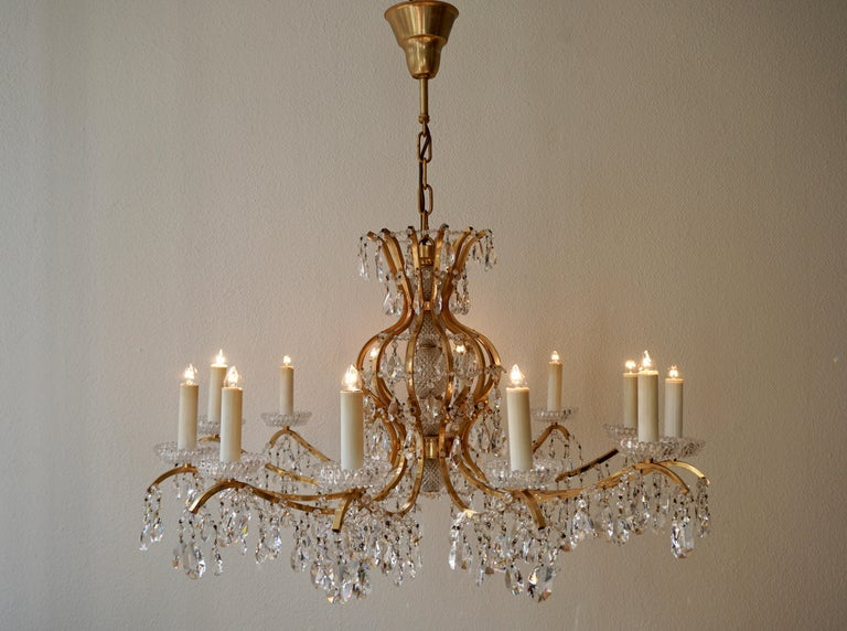 A fine twelve-light chandelier having a bright gilded brass frame and cut crystal dressing.