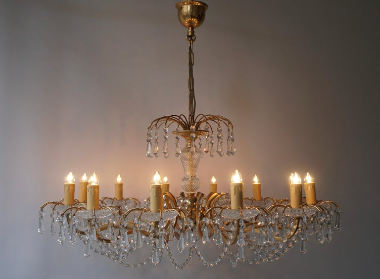 A fine twelve-light chandelier having a bright gilded brass frame and cut crystal dressing. Measures: Diameter 80 cm. Height fixture 40 cm. Total height including the chain and canopy 80 cm. Twelve E14 bulbs. Weight 6 kg.