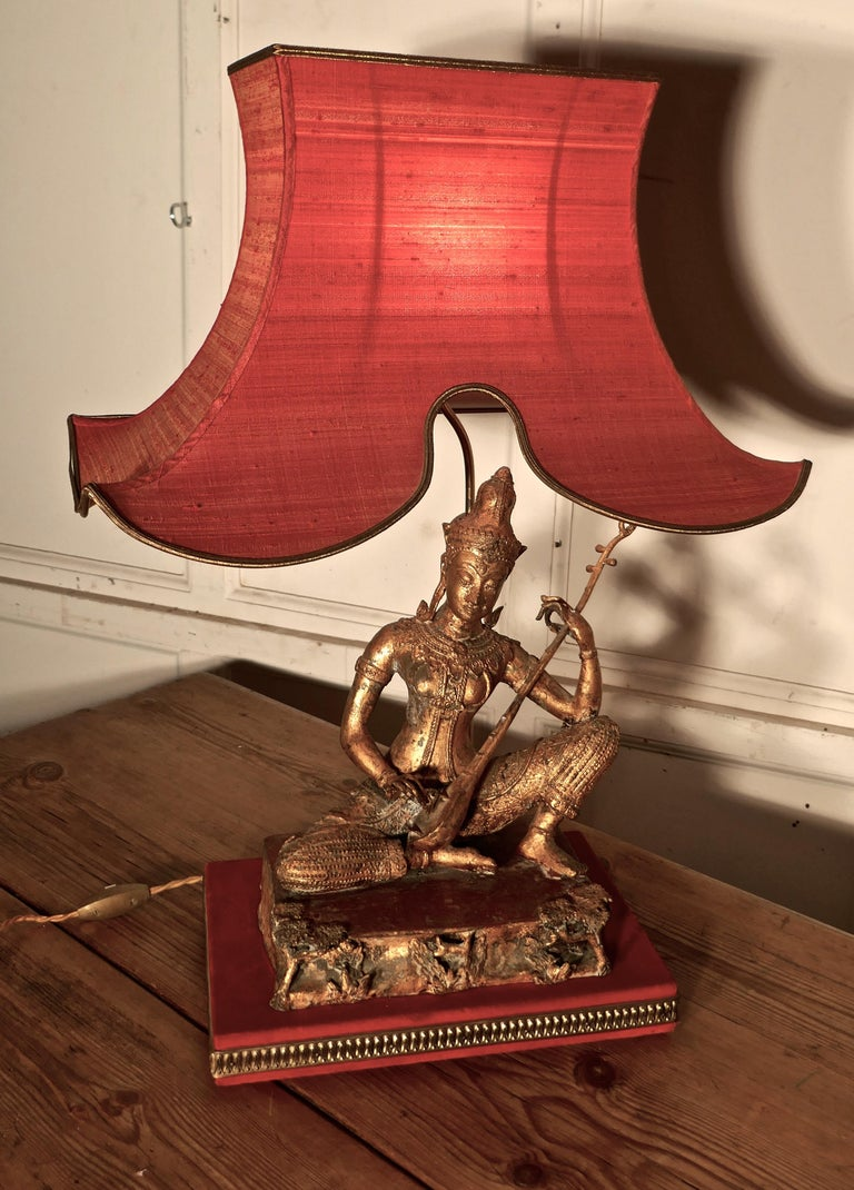 Gilded bronze seated Buddha table lamp   This is an excellent piece with an oriental theme  The Female bronze statue is seated playing a sitar, it has an old worn gold finish and this is set on a metal platform which is decorated in fine detail