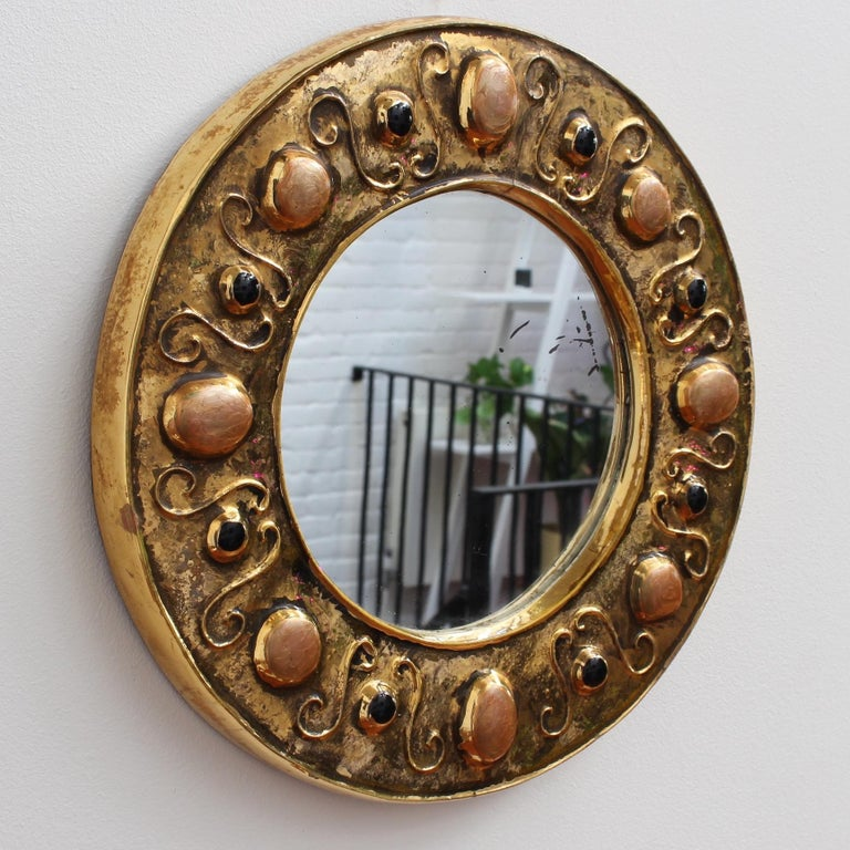 Gilded ceramic decorative wall mirror by François Lembo (circa 1960s-1970s). Porthole-shaped ceramic frame embellished with colourful enamelled cabochons in muted coral and black imitating natural stones. The piece is in fair vintage condition with