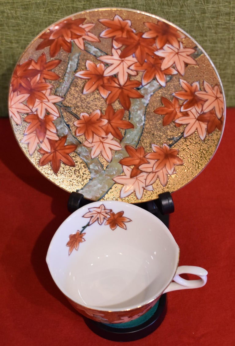Unique contemporary gilded fine porcelain cup and saucer, intricately hand-painted in iron-red and peach on an attractive gilded body, featuring autumn maple leaves. This cup and saucer is from a signature series by a highly acclaimed award-winning