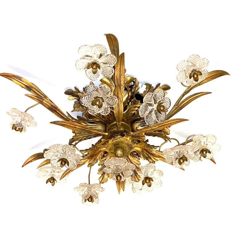 Add a touch of opulence to your home with this charming flushmount. Perfect gilt metal leafs with handmade Murano glass flowers to enhance any chic or eclectic home. We'd love to see it hanging in an entryway as a charming welcome home. Built in the