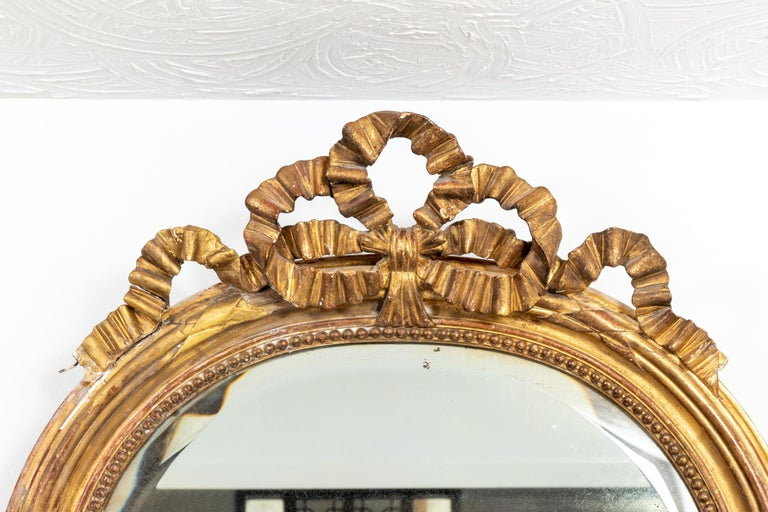 Late 19th century French oval shaped gilt mirror with bow crown. Wood frame and original glass. Restoration to gilt finish. Please note of wear consistent with age.