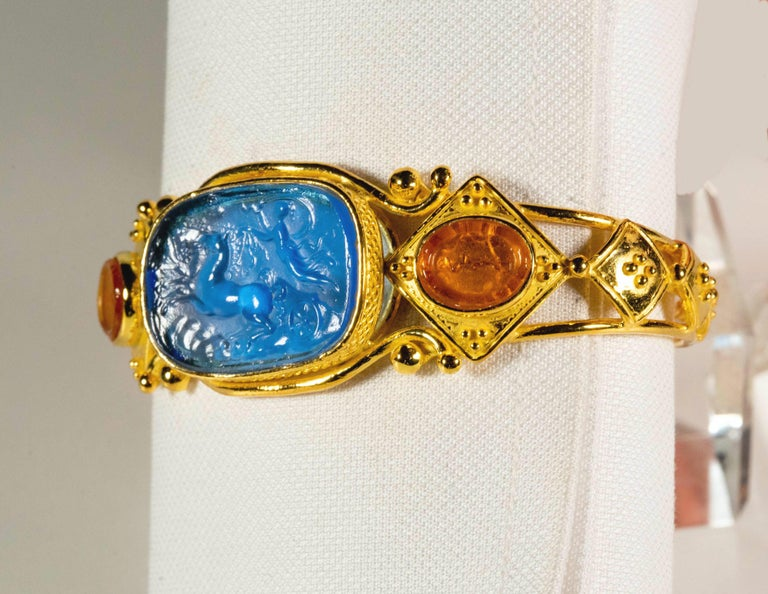 Gracious bracelet in gilded 925 silver with blue and orange cameos made of glass paste, inspired by Etruscan jewels. The decorative technique with which Etruscans and ancient Romans made the glass paste jewels, on which they depicted scenes of
