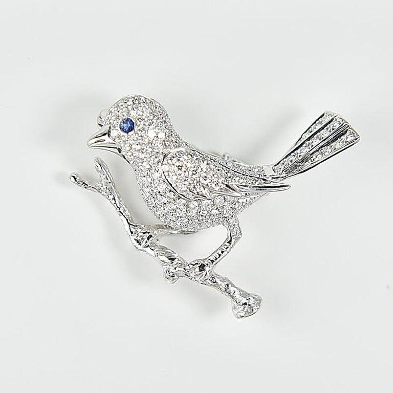 A delicate 18 Karat diamond brooch of bird design, with the tree branch handcrafted to create a sense of reality. This nature motif is given to life with a drop of sapphire blue. There are a total of 144 diamonds weighing approximately 0.93 carat,