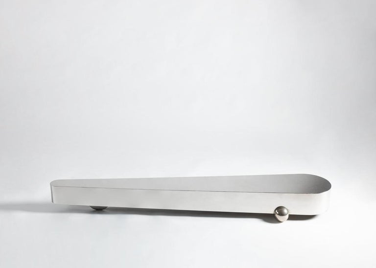 This sleek, stainless steel piece by Gilles Derain rests on two spherical shaped feet and a hidden support where one end narrows to a rounded point. It is veritably unique, breaking from all established expectations of what a coffee table is