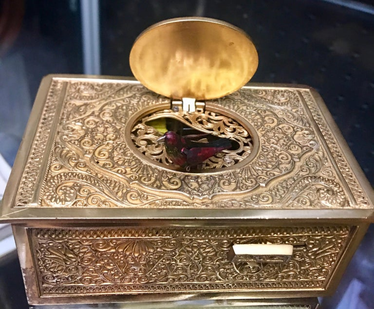 When wound and the actuation button slid to the right, the bird with layered feathered plumage in various red tones, gold gilt metal case, emerges moving polished metal beak, wings, tail feather and body from side-to-side to continuous synchronised
