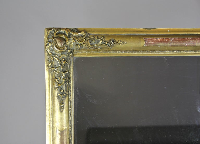 From France circa 1820 comes this fantastic gilt Biedermeier mirror. This breathtaking golden frame shows different gilding techniques like composition gold and gold leaf. Beautiful floral stucco works in each corner adorned by a gorgeous looking