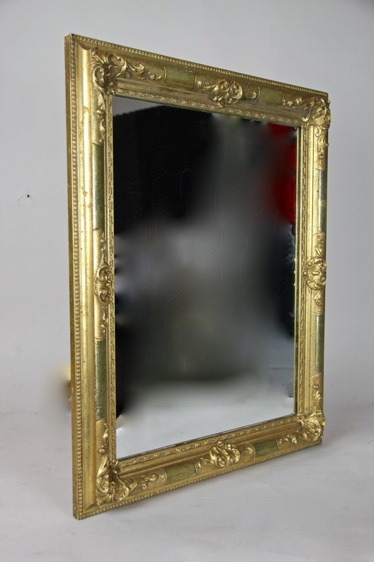 Remarkable gilt Biedermeier wall mirror from the later era circa 1850 in Austria. Nearly 170 year old, this great antique mirror was minimal restored by taking greatest care to keep its unique character. Only the mirror glass had to be renewed. The