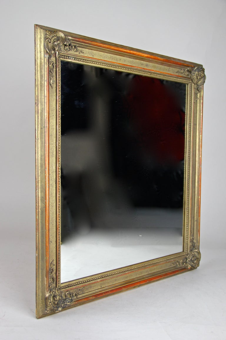 Gorgeous gilt Biedermeier wall mirror from the second period circa 1850 in Austria. This dreamlike masterpiece shows different kind of gilt techniques. The frame impresses with wonderful stucco applications in the corners and gold leaf covered outer