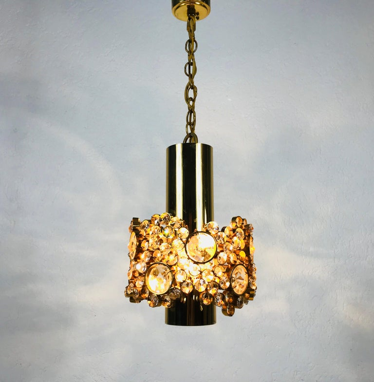 An extraordinarry pendant lamp by Palwa made in Germany in the 1970s. The lamp has a very elegant design. It is made in the period of Hollywood Regency. Round Gilt brass body with one E27 socket. The socket is surrounded with very elegant crystals.