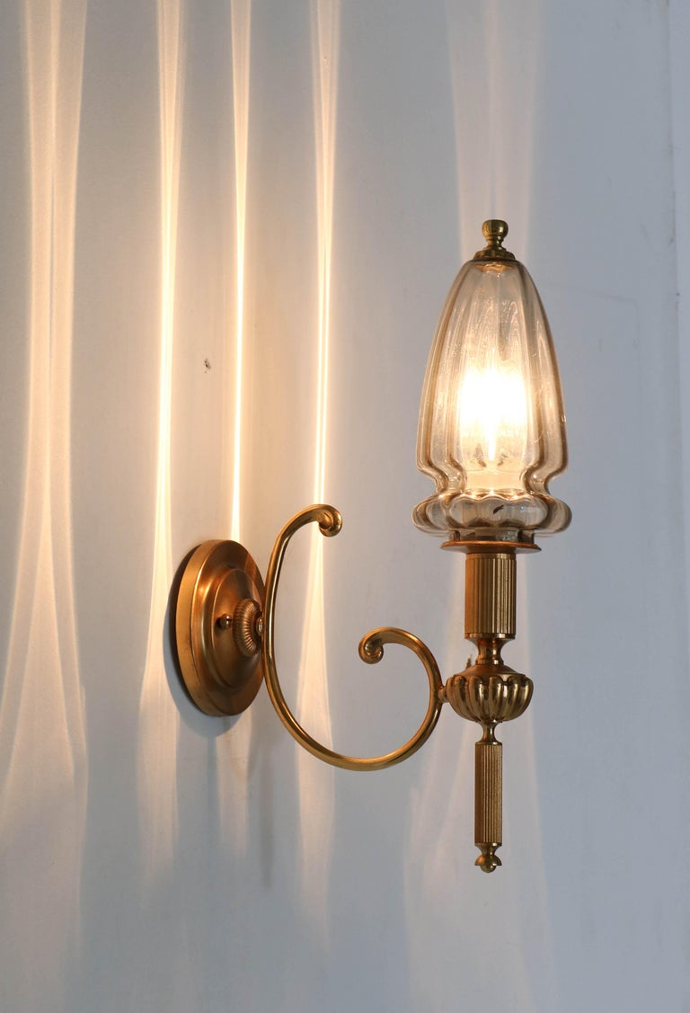 Wonderful and rare Hollywood Regency wall light or sconce. Design by Gaetano Sciolari. Striking Italian design from the 1970s. Gilt brass with original glass shade. Marked with label Sciolari. In good original condition with a beautiful patina.